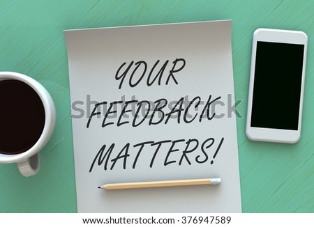 Your Feedback Matters, message on paper, smart phone and coffee on table - stock photo