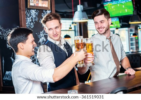 Your health. Four friends men drinking beer and having fun together in the bar