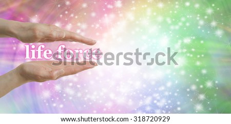 Your Life Force is in Your Hands - Female parallel hands with the words 'life force, floating between surrounded by a sparkles on a pastel colored  background and plenty of copy space - stock photo