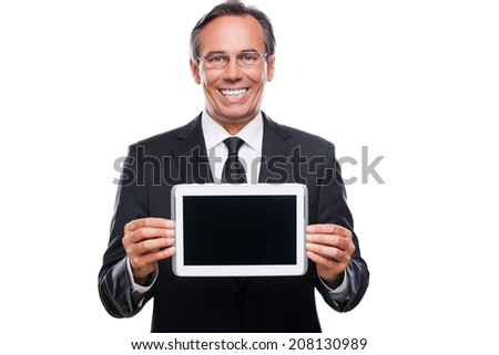 Your message on his tablet. Confident mature man in formalwear and glasses showing monitor of his digital tablet and smiling while standing isolated on white background - stock photo