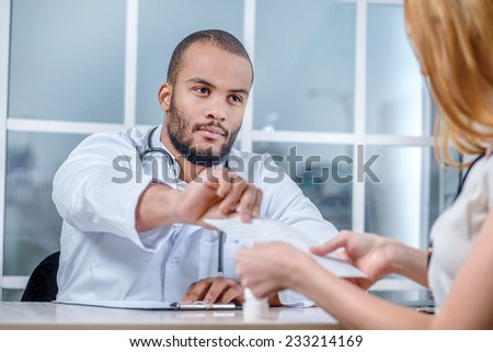Your treatment in the prescription.  The doctor prescribes drugs and pills on the table right in front of the patient writing his medical prescription drug in the office and hands it to the patient - stock photo