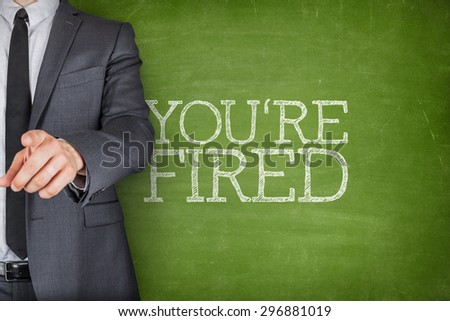 Youre fired on blackboard with businessman finger pointing - stock photo