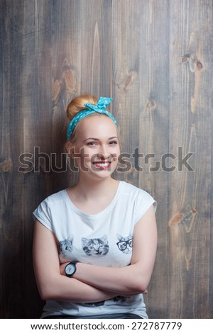 Youth and confidence. Portrait of young attractive smiling woman looking at camera leaning on wooden wall. - stock photo