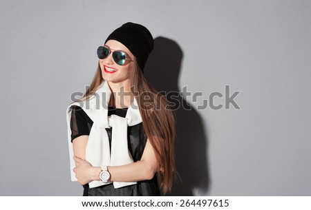 Youth and fashion. Be trendy! Attractive young smiling woman in hat and sunglasses standing against grey background. - stock photo
