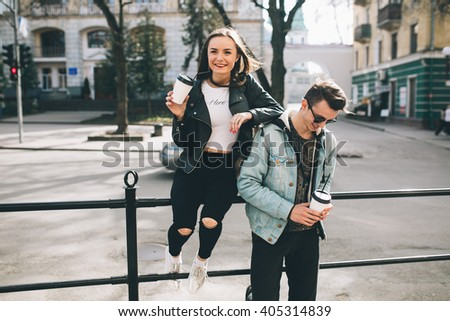 Youth and fashionable couple on the streets drinking coffee.
