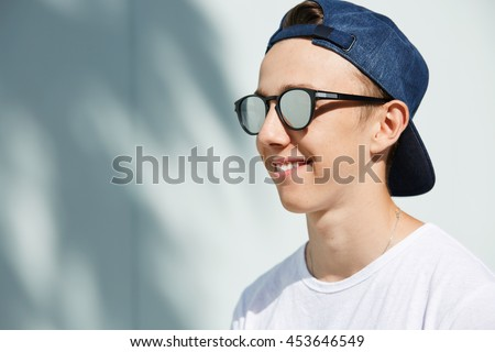 Youth and happiness. Close up profile of fashionable 15-year old student boy with healthy clean skin wearing snapback backwards, standing against white copy space wall for your promotional content - stock photo