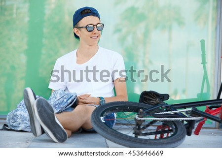 Youth and happiness. Happy 15-year old student wearing snapback and shades, smiling, looking away, enjoying summer vacations, sitting in the shadow with his fixed gear bicycle lying beside him - stock photo