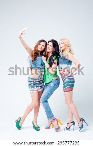 Youth and technology. Full length studio portrait of Three beautiful young women laughing and taking selfie on smartphone together. - stock photo