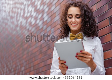Youth and technology. Young attractive brunette woman using tablet computer against brick wall. - stock photo