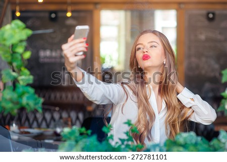 Youth and technology. Young beautiful long hair woman taking selfie by smartphone while sitting at cafe. - stock photo