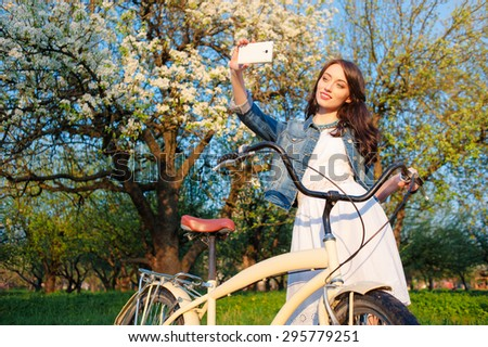 Youth and technology. Young smiling woman with bicycle taking selfie  while standing in blossom garden.