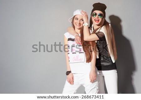 Youth and urban fashion. Attractive twins sisters. Two beautiful smiling young women having fun together. - stock photo