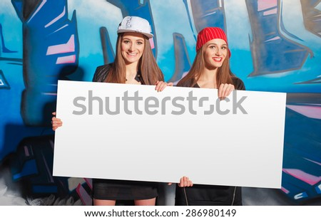 Youth and urban fashion. Attractive twins sisters. Two beautiful smiling young women holding blank with copy space together. - stock photo