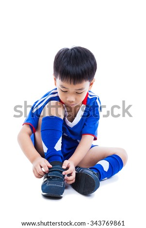 Youth asian (thai) soccer player in blue uniform tying shoe before playing soccer with drop shadow. Child preparing ready for competition. Sport lifestyle. Isolated on white background.
