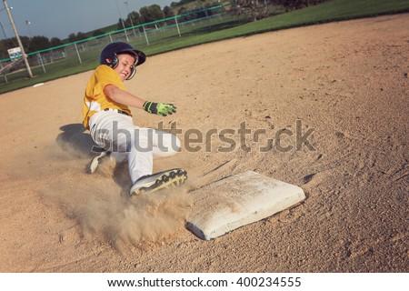 Youth Baseball playing sliding back to base. focus on base and foot - stock photo
