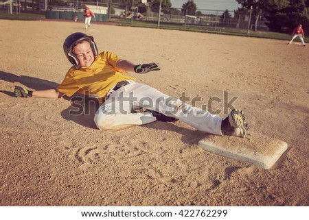 Youth Baseball playing sliding to second base. - stock photo