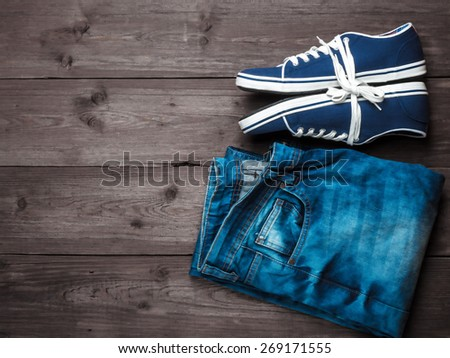 Youth blue sneakers with tied laces and blue jeans with scuffed on wooden background - stock photo
