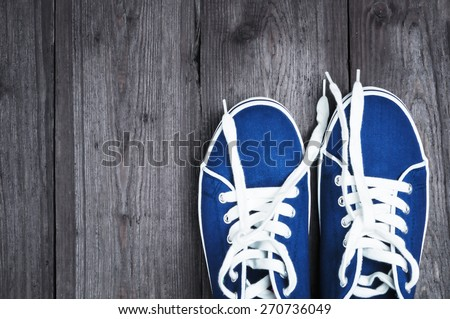 Youth blue sneakers with white untied the laces on wooden background - stock photo