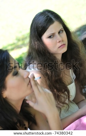 Youth culture - two young people outdoors, one woman smoking cigarette annoys and irritates another girl - stock photo
