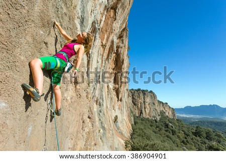 Youth female Rock Climber hanging on vertical Wall expressing Joy and Satisfaction Mountains and Blue Sky Background - stock photo