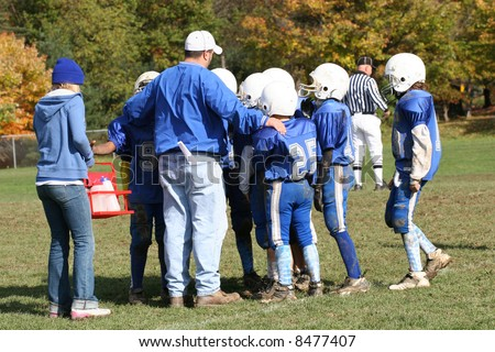 Youth Football Huddle with Coach - stock photo