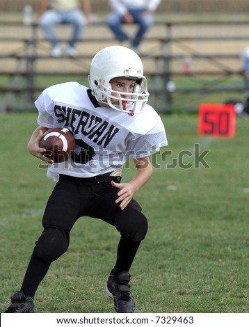 Youth football player crossing the 50 yard line on a running play. - stock photo