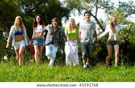 Youth group running on a grass against the nature - stock photo