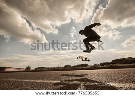 Youth, leisure, recreation, hobby, active lifestyle and extreme sports. Outdoor portrait of silhouette of teenage boy jumping high with skate in the air going to land on board while doing kick flip