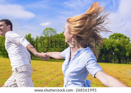 Youth Lifestyle: Caucasian Couple Relaxing Outdoors. Man Dragging Her Lady by Hands.  Holiday and Vacation Concepts. Horizontal Image Composition - stock photo
