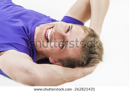 Youth Lifestyle Concept: Happy Smiling Tanned Handsome Man Lying on Floor with Hands Folded Behind His Head. On white Background. Horizontal Image Composition - stock photo