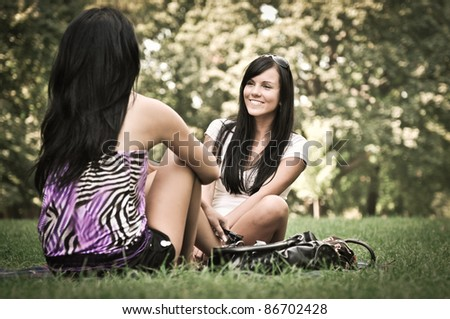 Youth lifestyle park scene - two young friends (girls) talking outdoors. Siting on rug laid in grass.