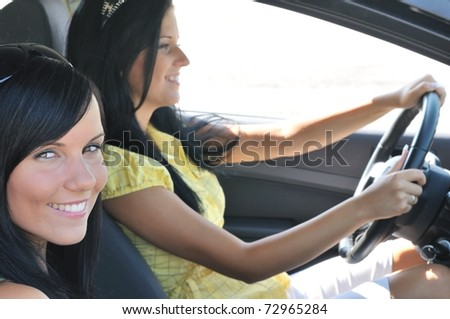 Youth lifestyle - two smiling friends (women) driving in car - stock photo