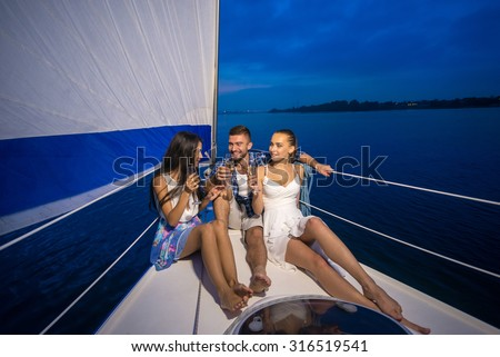 Youth party on a yacht. Friends drinking champagne. Night walk on a yacht. - stock photo