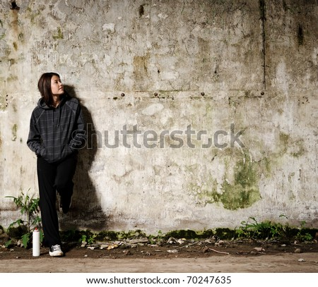 Youth planning a graffiti mural on a vacant, empty wall - stock photo
