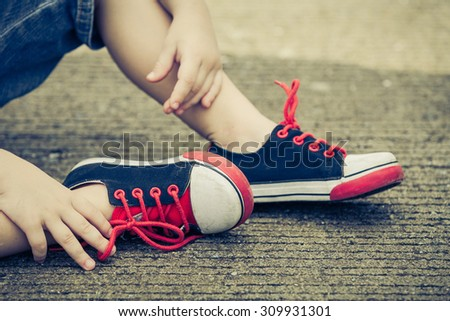 youth sneakers on boy legs on road during sunny  summer day. - stock photo
