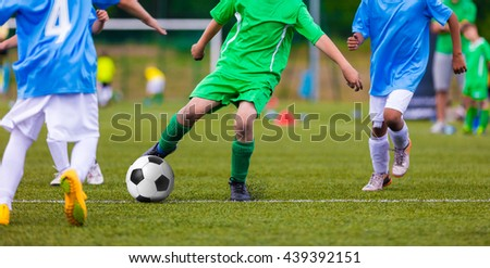 Youth soccer football teams kicking soccer ball on a sports pitch. Soccer tournament for young footballers. - stock photo
