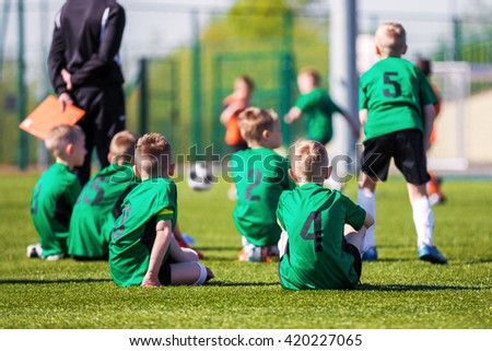 Youth soccer team together watching football game. Soccer tournament for young players. Boys sitting on a sports field and supporting team. - stock photo