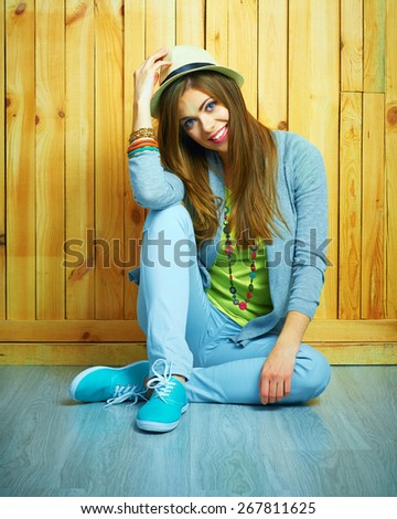Youth style portrait of young woman sitting on a floor. Teenager girl portrait. Wooden background.