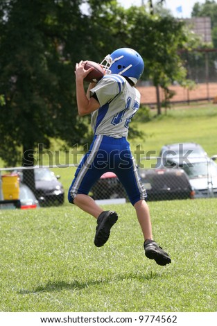 Youth Teen Football Player Catching Football during Game. - stock photo