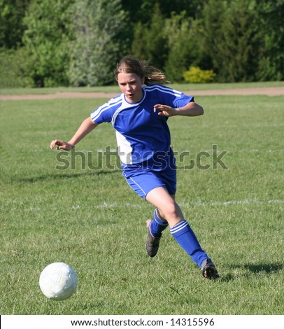 Youth Teen Girl Chasing Soccer Ball Down the Field - stock photo
