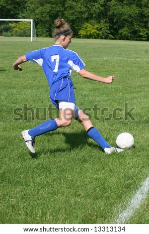 Youth Teen Soccer Player in Action on field during game. - stock photo