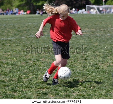 Youth Teen Soccer Player Kicking Ball on Field During Game. - stock photo