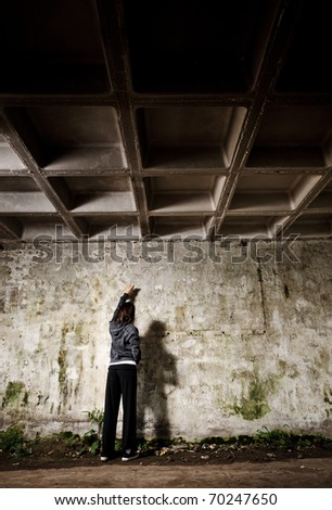 Youth with spray paint busy making graffiti art on an empty wall - stock photo