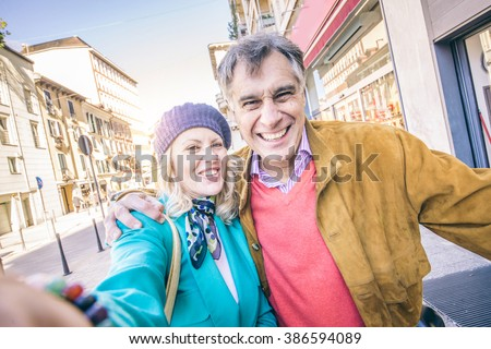 Youthful senior couple taking selfie outdoors - Happy mature pair having fun while walking on the streets outdoors - stock photo