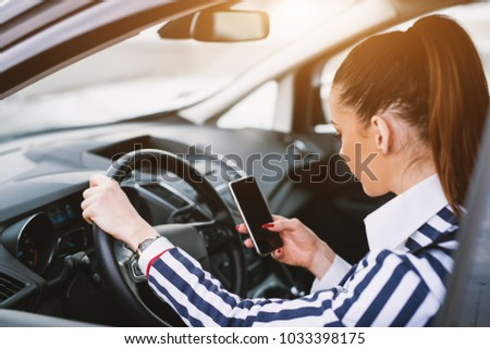 Youthful woman texting from her cell phone while sitting in the car.