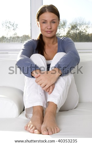 Yoyng yoman sitting in living room smiling - stock photo