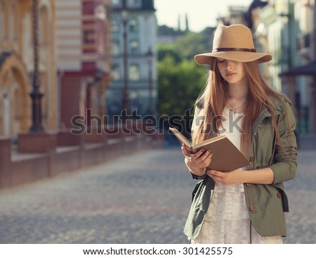 Yuccie girl reading book outdoors - stock photo