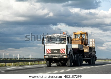 YUGRA, RUSSIA - AUGUST 4, 2012: Semi-trailer truck MAZ 6425 carries a bulldozer T-170 at the interurban road. - stock photo