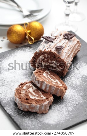 Yule log cake decorated with chocolate leaves on a Christmas table - stock photo