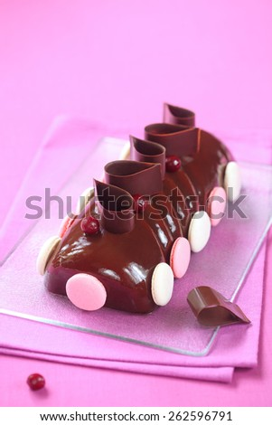 Yule Log Cake glazed with chocolate mirror glaze, decorated with chocolate loops, cherries and french macarons, on a transparent cutting board and bright pink background. - stock photo